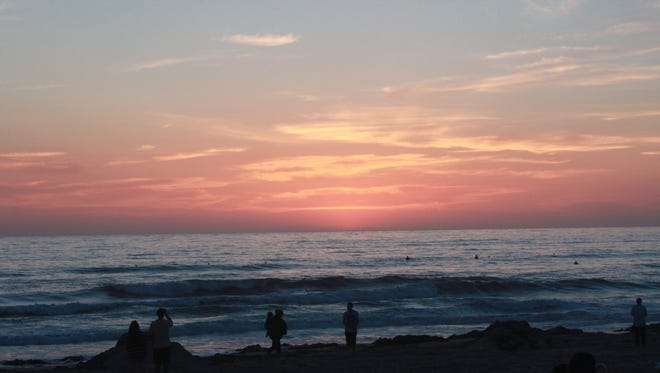 Stragglers watch the sun set over Pacific Beach.