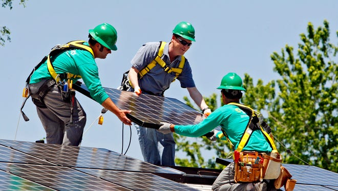 FILE - In this June 18, 2010, file photo, U.S. Senator Michael Bennet, D-Colo., center, helps as Solar City employees Jarret Esposito, left, and Jake Torwatzky, right, install a solar panel on a home in south Denver. The solar panel installer SolarCity said Wednesday, Jan. 15, 2014, it will launch an investment platform that will allow individuals and others to invest in rooftop solar systems directly with SolarCity. (AP Photo/Ed Andrieski, File) ORG XMIT: NYBZ130
