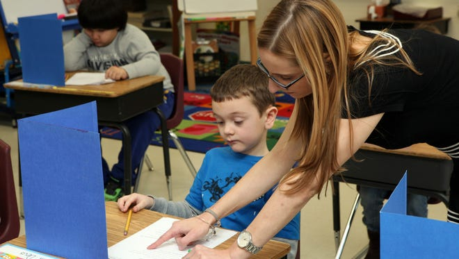 Student teacher Samantha Felder works with a first-grader at the Park Avenue School in Port Chester Feb. 27, 2014. Felder is completing a master's degree at Manhattanville College and is preparing for a new exam in order to get her initial certification to teach in New York State.