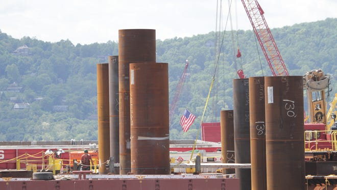 Contractors work alongside pilings on May 30 as construction continues on the new Tappan Zee Bridge.