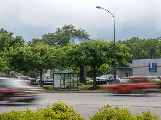 Cars drive by the empty Electric City Transit bus stop on North Main Street in Anderson on Wednesday. The high-traffic area in front of the Goodwill Store near Whitehall Road, many drove by emergency workers working at the scene where homeless woman Sheila Renee Poole was found dead at an Anderson bus stop on Tuesday.