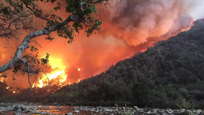 A wildfire approaches the Kings River east of Fresno, Calif., Sept. 19, 2015.