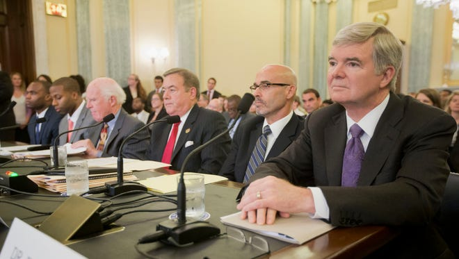 NCAA President Mark Emmert, right, waits to testify on Capitol Hill. From left are, Myron Rolle, former Florida State football player, former North Carolina football player Devon Ramsay, former athletic former Temple athletic director William Bradshaw and university of South Carolina professor Richard M. Southall.