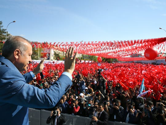 Turkish President Recep Tayyip Erdogan waves to supporters