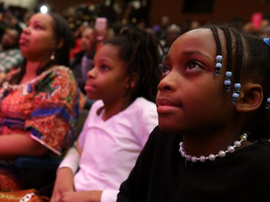 Alyce Smith of Detroit watches with others as the drum group Nano Djipo performs during a Kwanzaa celebration inside the Charles H. Wright Museum of African American History in Detroit on Saturday, Dec. 26, 2015