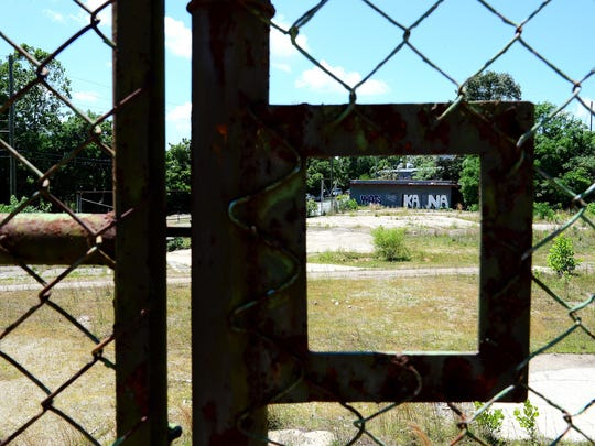 An empty lot slated to become RAD Lofts on the corner of Clingman Avenue and Roberts Street viewed through a window in the fence.