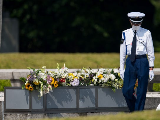 A policeman checks the flowers at the cenotaph at the
