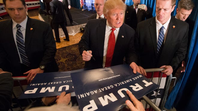 Republican presidential candidate Donald Trump signs autographs during a campaign stop at the Radisson Hotel, Friday, Jan. 29, 2016, in Nashua, N.H.