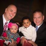 Brian Copeland holds daughter Esther as husband Greg Bullard holds son Micah.