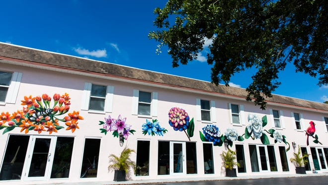 A mural depicting flowers decorates the side of Naples Beach and Bay Realty in the Bayshore Arts District of Naples on Monday, April 2, 2018.