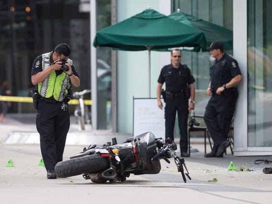A police officer photographs a motorcycle after a female