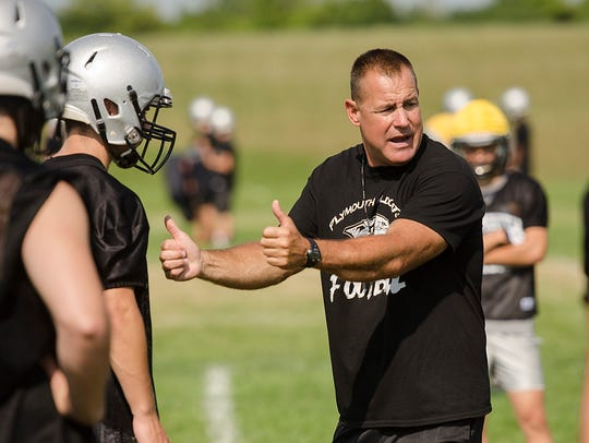Plymouth football coach Mike Sawchuk works with the