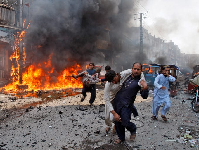 Injured men are carried away from the site of a blast shortly after a car explosion in Peshawar, Pakistan, on Sept. 29. Scores of people were killed in the third blast to hit the troubled city in a week.