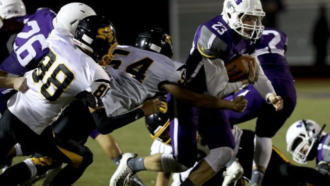 Greg Barnette/Record SearchlightShasta's Gideon Magrini (right) runs past Enterprise defenders Anthony Sarmanto (left) and Dillon Starnes during the River Bowl on Friday night.