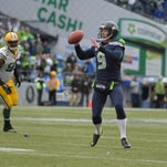 Jan 18, 2015; Seattle, WA, USA; Seattle Seahawks punter Jon Ryan (9) throws a 19 yard touchdown pass on a fake field goal past Green Bay Packers defensive end Datone Jones (95) and Davon House (31) during the third quarter in the NFC Championship Game at CenturyLink Field.