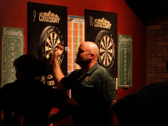 Kevin Krell removes his darts from a board inside the BackStreets Sports Bar, one of the establishments permitted for extended hours in Cape Coral.