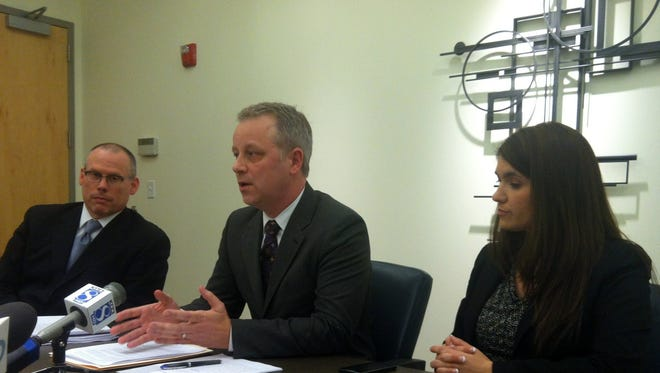 Joseph Walsh, center, speaks at a news conference with his lawyer, Michael Carroll, and his wife, Venus Vendoures Walsh