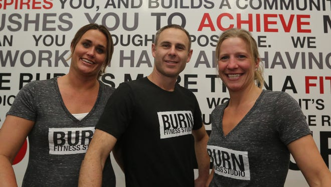 Rebecca and Jason Lowman (from left), co-owners of Burn Fitness studio in Weston, stand in front of one of their walls featuring a motivational message on Friday, along with studio manager Sarah Riley.