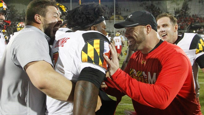 Maryland strength coach Rick Court (right) congratulates quarterback Tyrrell Pigrome after the freshman scored during the second overtime of a 30-24 victory over Central Florida at Bright House Networks Stadium.on Sept. 17.