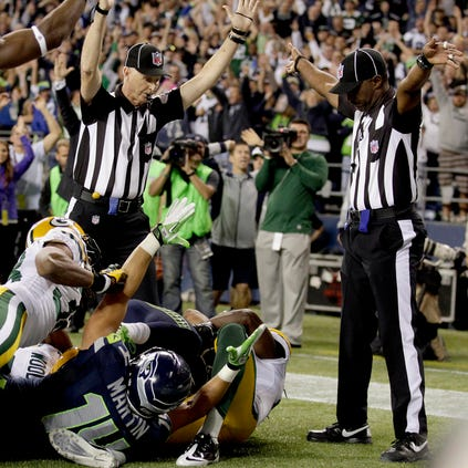 Official Lance Easley signals a touchdown by Seahawks wide receiver Golden Tate, obscured, on the last play of the game on Sept. 24, 2012, in Seattle.