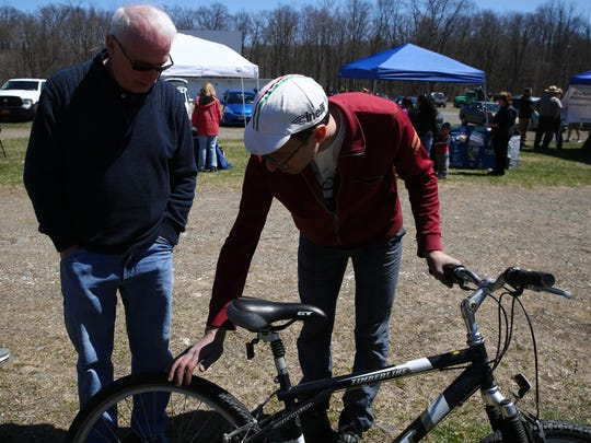 John Galbraith of Spoke, right, accepts a bike donation from Hyde Park resident Alan Woodward at an Earth Day recycling event in Hyde Park on Saturday.
