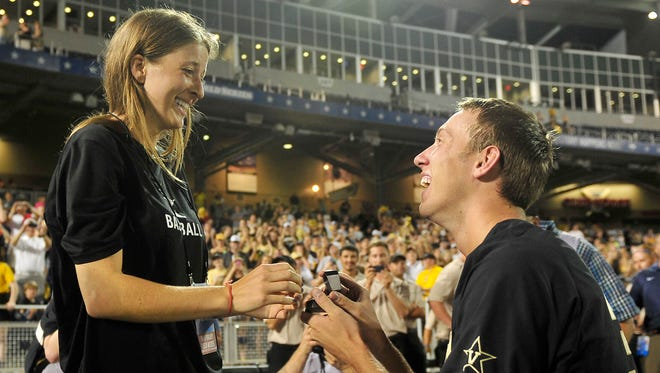 Vanderbilt pitcher Brian Miller, right, proposes to Megan Bonds after winning the College World Series Championship at TD Ameritrade Park in Omaha, Neb., Wednesday, June 25, 2014.