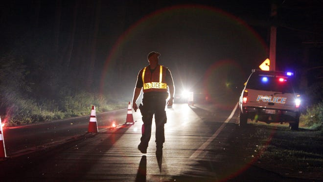 A North Castle police officer walks up to a vehicle during a DWI checkpoint.