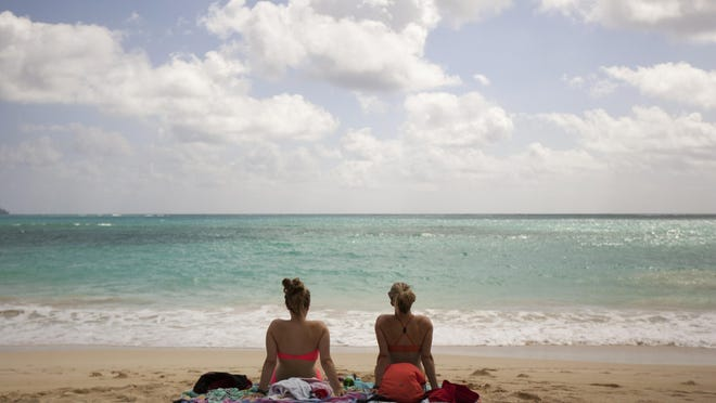 Ali Junell of Portland, left, and Kristen Carmichael, of Los Angeles, sit on the beach at Waimanalo Bay Beach Park in Waimanalo, Hawaii. The beach was listed as No. 1 on the 2015 list of best beaches, a list compiled annually by Florida International University Professor Stephen Leatherman, also known as Dr. Beach.