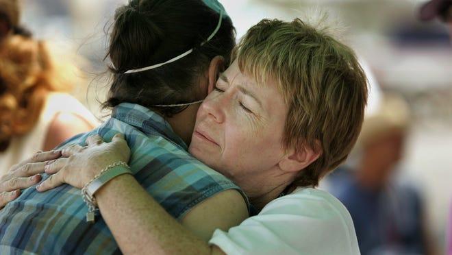 Karen Stewart of Eisenhower Medical Center hugs a local resident of Waveland, during a vaccination clinic at 'Camp Katrina.' Sept. 15, 2005.
