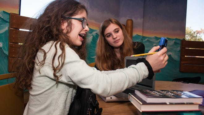 Middle school student, Lilian Timpone (R), 12, shows pictures of her trip to New York Comic Con to her Homework Helper tutor, Sam Colvin, 17, Thursday, Oct. 15, 2015, in Manalapan, N.J. (Contributor/EvaJo Alvarez)
