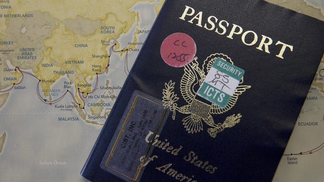 Pricilla Dickson's passport sits on top of a map showing the route of their round the world cruise Wednesday.