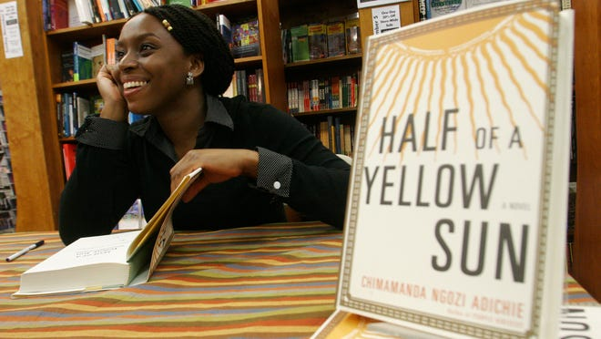 FILE- In this Tuesday, Oct. 10, 2006, Nigerian author Chimamanda Ngozi Adichie autographs copies of her novel, Half of a Yellow Sun, after a reading at Harvard Bookstore in Cambridge, Mass. Nigerian censors are effectively banning the film ìHalf of a Yellow Sunî and will not even say why, the Nigerian-British producers told The Associated Press Thursday amid suspicions that censors fear it could rouse tribal rivalries. The National Film and Video Censor Board insisted it has not banned the movie but delayed its registration over ìsome unresolved issues which have to be sorted out.î The movieís Nigeria premiere was set for last Friday. Invitations had been sent out and the film was to play in every cinema in the country. On Thursday, the board told the distributors that the film had not yet passed the registration process. ìNo the film hasnít been banned but we canít show it, which technically is a ban,î Biyi Bandele said in a telephone interview from his home in London, where the movie placed among the 10 most popular at cinemas over the Easter weekend. It stars Oscar nominee Chiwetel Ejiofor and Thandie Newton and is an adaptation of the book by prize-winning novelist Chimamanda Ngozi Adichie. (AP Photo/JB Reed, file) ORG XMIT: NIN104
