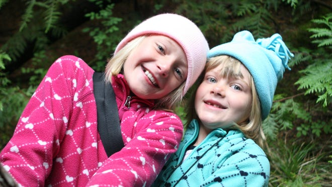 Lizzie, left, and Hallie Thompson play around while camping at Fish Creek Campground in Glacier National Park in 2010. They were 7 and 5 years old.