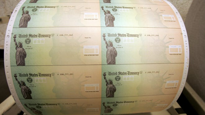 FILE - In this May 8, 2008 file photo, blank U.S. Treasury checks are seen on a roll at the Philadelphia Financial Center, which disburses payments on behalf of federal agencies, in Philadelphia.