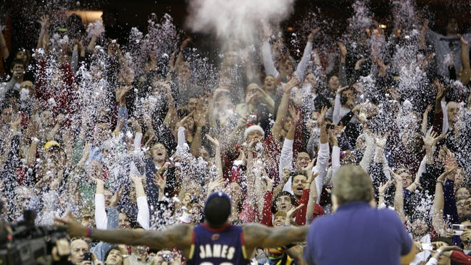 In this Dec. 25, 2008, file photo, fans toss confetti to mimic the Cleveland Cavaliers' LeBron James's pre-game chalk toss before an NBA game against the Washington Wizards in Cleveland. Billions has been spent on state-of-the-art sports facilities over the last quarter-century, but there is no way to prevent the potential spread of a virus through coughing or sneezing. Officials are working on safety protocols and looking at new technology in hopes of making stadiums and arenas as safe as they can.
