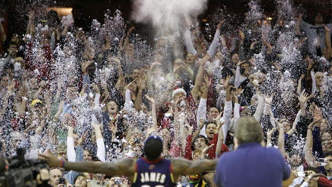 FILE - In this Dec. 25, 2008, file photo, fans toss confetti to mimic Cleveland Cavaliers' LeBron James's pre-game chalk toss before an NBA basketball game against the Washington Wizards in Cleveland. Billions has been spent on state-of-the-art sports facilities over the last quarter-century, but there is no way to prevent the potential spread of a virus through coughing or sneezing. Officials are working on safety protocols and looking at new technology in hopes of making stadiums and arenas as safe as they can.