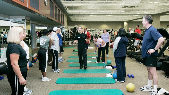 A personal trainer at Lifetime Fitness in Rochester Hills works with patrons in a fitness/wellness class in this 2006 file photo.
