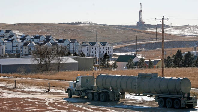 In this Feb. 26, file photo, an oil truck sits in a dirt lot near a new housing development in Watford City, N.D. The United States is still growing older, but the trend is reversing in the Great Plains, thanks to a liberal application of oil.