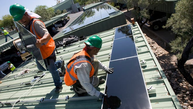 160309  biz-solarfight0820  08/17/09  SolarCity (cq is one word) workers Gabriel Flores (cq) on left, and Tony Gomez (cq) putting solar panels on the garage roof at National Bank of Arizona(cq)head office  in Phoenix (cq). Companies that install solar panels on houses are gearing up for a fight with regulators about how APS must spend its money earmarked for renewable energy. The debate is whether APS should spend more money on rebates for houshold solar systems or bigger systems that go on businesses, like the bank project.  Some Corporation Commissioners say that the big systems are a better use of the money, because they produce more electricity for a better price than several household power systems.  Photo by Nick Oza/ The Arizona Republic