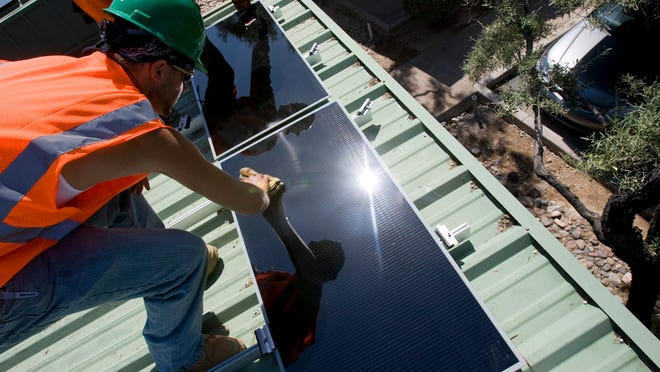 FILE PHOTO: SolarCity workers Tony Gomez (in back) and Shawn Huggins put  solar panels on the garage roof at National Bank of Arizona head office in Phoenix.