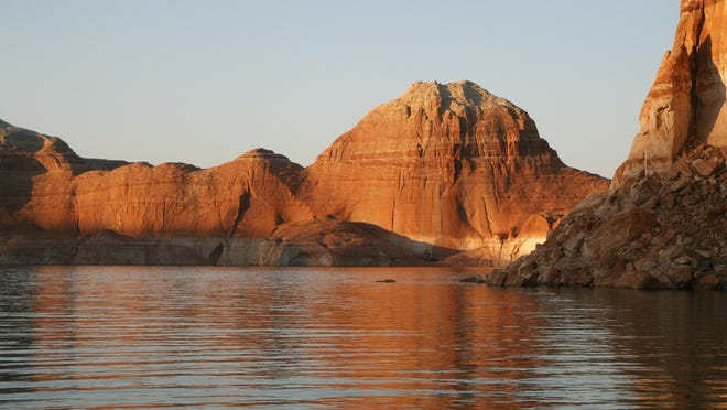 The late afternoon sun illuminates the cliffs of Padre Canyon and the waters of Lake Powell in this 2008 file photo.