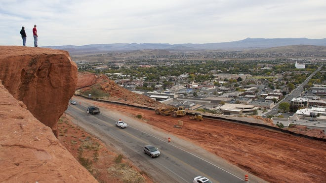 "Visitors standing atop the ""Sugarloaf"" or ""DIxie Rock"" at St. George's Pioneer Park look out over the central part of the city."