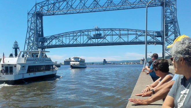 Duluth natives and tourists flock to the city's iconic Aerial Lift Bridge which raises the road bed 135 feet to allow giant freighters into the busiest harbor on the Great Lakes.  For smaller vessels such as these excursion boats, the bridge stops at this lower height.
