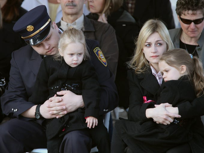The family of Mike Chiapperini, including his wife Kim and son Nick with his daughters Kylie, 3, and Kacie, 4, during the memorial sign ceremony on Lake Road in Webster on April 15, 2013.