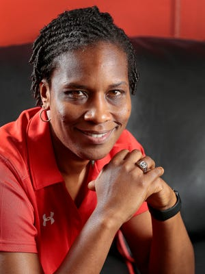 University of Cincinnati women's basketball head coach Jamelle Elliott poses with the national championship ring she won as a player at the University of Connecticut, the first of her six national title rings, in her office in the Lindner Center on UC's main campus in Cincinnati on Wednesday, Aug. 31, 2016. Elliott recently returned to Cincinnati from Brazil where she was an assistant coach on the gold medal-winning US women's Olympic team in Rio de Janeiro.
