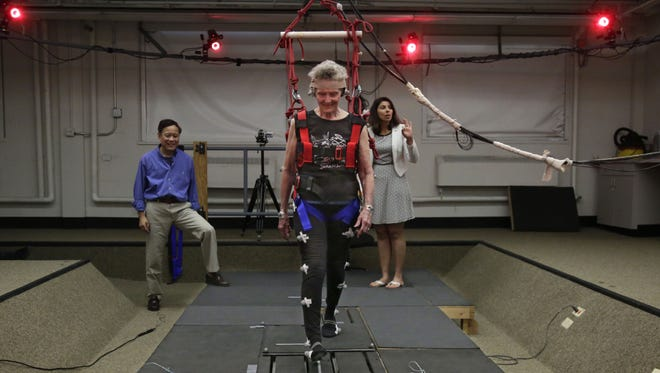 This July 28, 2014 photo shows Clive Pai, a University of Illinois-Chicago physical therapy professor, left, and physical therapy assistant professor Tanvi Bhatt, right, watching Mary Kaye, 81 as she demonstrates a treadmill balance session at the school in Chicago.