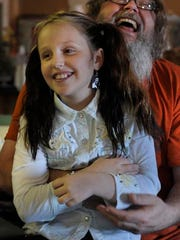 Emi Sunshine Hamilton, 10,  has a laugh with her father Randall during a band meeting on Monday Nov. 10, 2014, in Madisonville in Tenn.