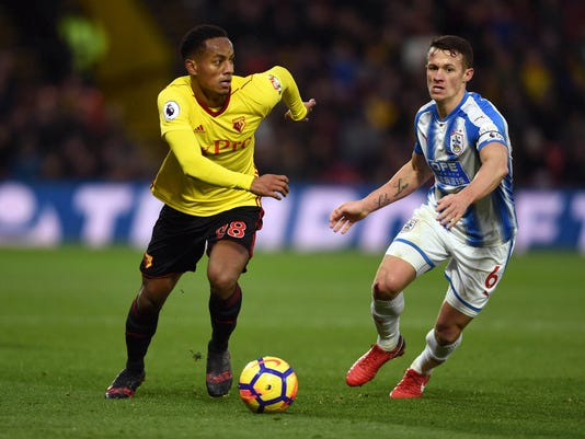 Watford's Andre Carrillo, left, and Huddersfield Town's Jonathan Hogg battle for the ball during the English Premier League soccer match at Vicarage Road, Watford, Saturday, Dec. 16, 2017. (Daniel Hambury/PA via AP)
