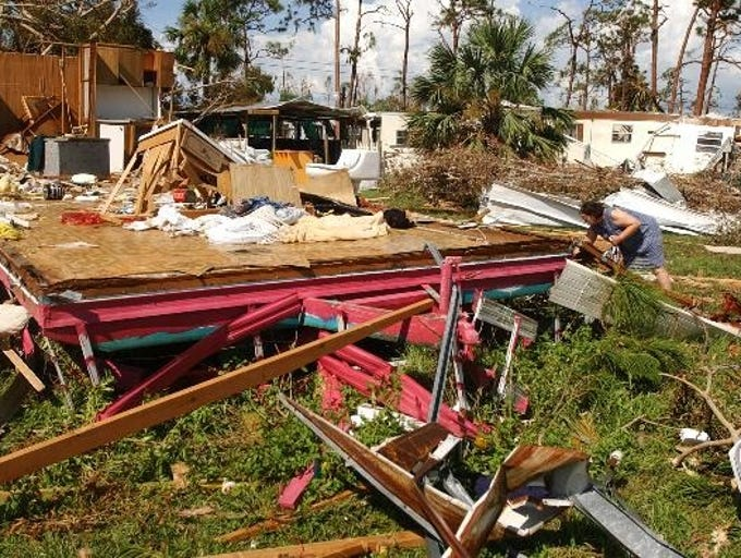 Vivian Palmeiro-McGee searches for belongings in her destroyed mobile home on Raymary Street on Pine Island on Sunday. She and her father rode out the storm in their vehicle right next to the home.