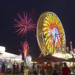 A fireworks show at the Michigan Challenge Balloonfest gives those riding the Wade Shows carnival rides an added spectacle after a number of balloons inflated, but stayed tethered due to a strong winds.